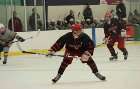 Jack Wojnowski, sophomore, skates down the ice to get the puck.