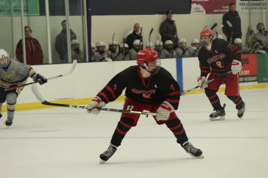 Jack Wojnowski, sophomore, skates down the ice to get the puck.
