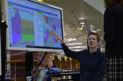 Jack Wypiszynski, senior, kneels down near a map to point out his results on Gerrymandering in Wisconsin
