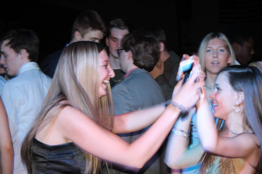 Olivia Sullivan and Annie McCormick, seniors, share a laugh on the dance floor.
