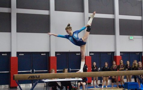 Taylor Raskin, senior, performs on the beam during a home meet.