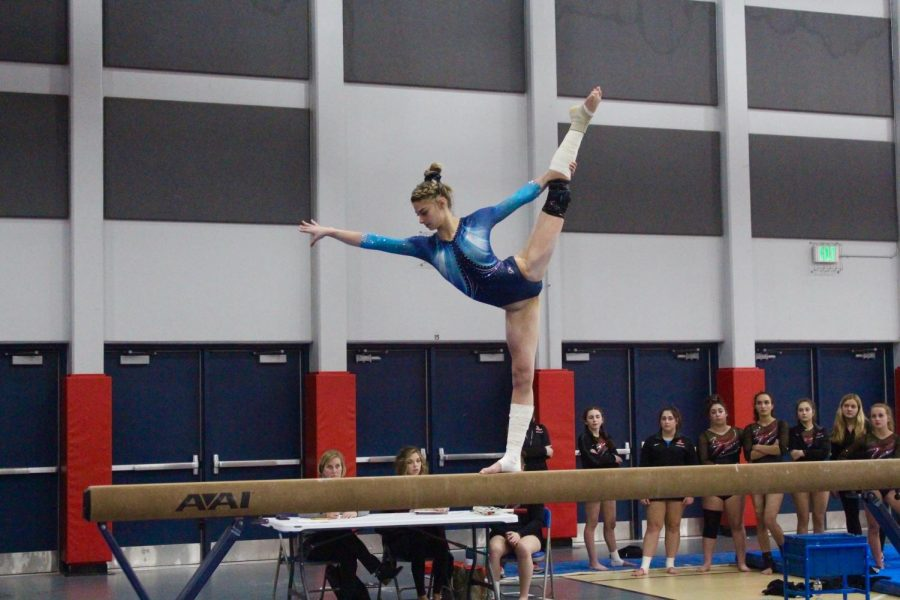 Taylor+Raskin%2C+senior%2C+performs+on+the+beam+during+a+home+meet.