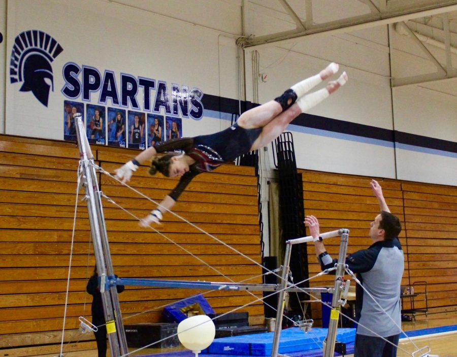 Taylor Raskin, senior, completes a skill on the uneven bars, her favorite event.