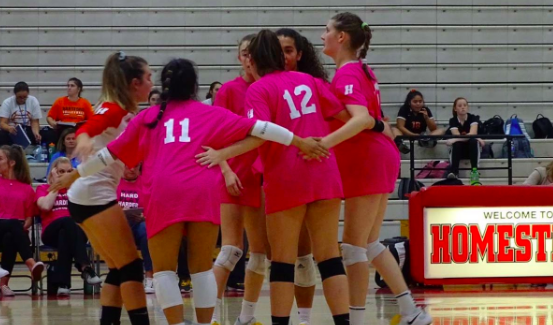 Members of the Homestead High School girls volleyball team huddle together in between plays.