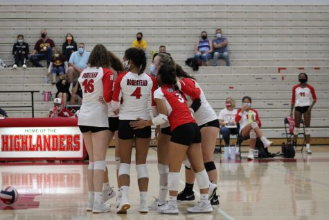 The girls volleyball team celebrates together after scoring a point in their first home game.