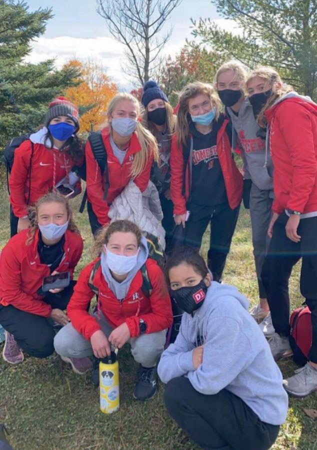The+girls+cross+country+team+poses+with+their+masks+on+after+qualifying+for+state.