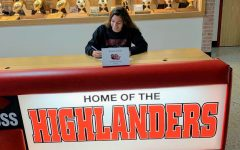 Theadora Krueger smiles as she signs her commitment paper to play lacrosse at Davenport University.