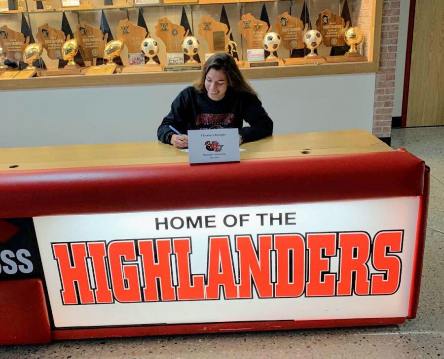 Theadora+Krueger+smiles+as+she+signs+her+commitment+paper+to+play+lacrosse+at+Davenport+University.+
