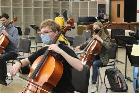 Orchestra students practice their instruments during class.