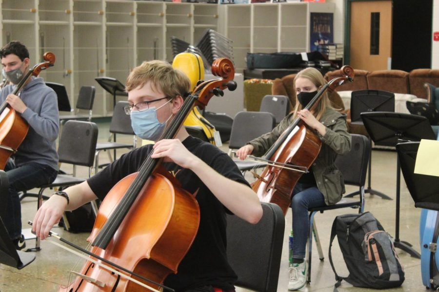 Elan Levin, senior, plays cello during in person orchestra class.