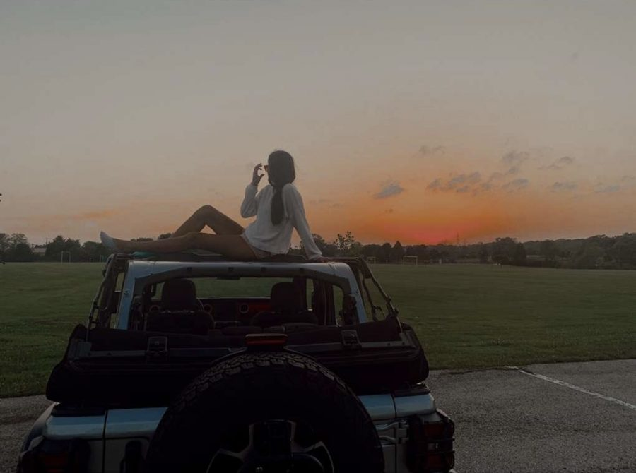 Rayen sits on her jeep enjoying the beautiful sunset.