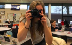 Hannah Kennedy, senior, takes a photo in her journalism class.
