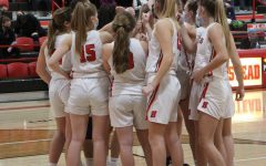 The girls basketball team huddles together during their game on Friday night.