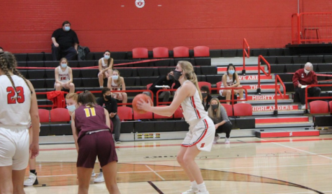 Senior Lexi Buzzell steps up to the line for a shooting foul against West Bend East while her team sits (socially distanced) behind her.
