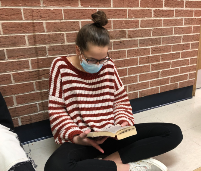 Luedtke participates in reading time in the hallway outside her class.