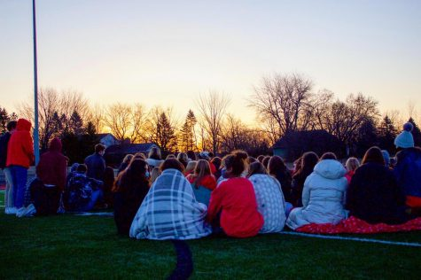 Seniors gather on the football field to watch the sunrise together.