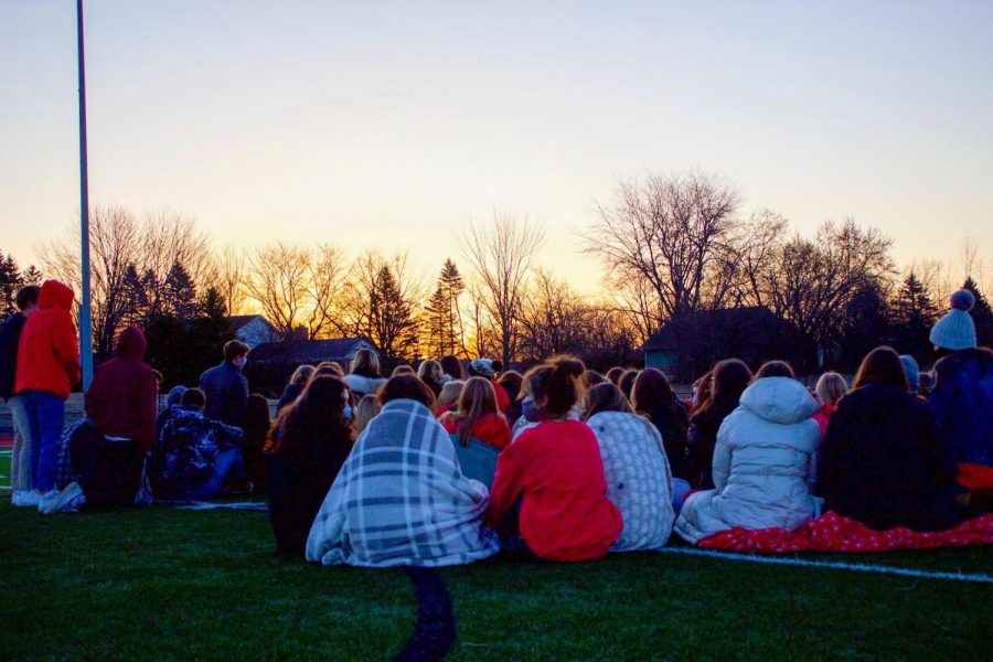 Seniors+gather+on+the+football+field+to+watch+the+sunrise+together.+