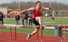 Ryan Gettlefinger, senior, jumps  the final hurdle in the 100-meter sprint.
