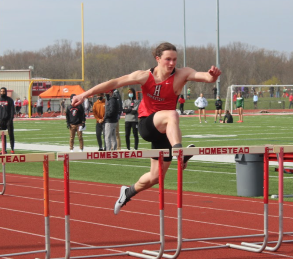 Ryan Gettlefinger, senior, jumps  the final hurdle in the 100-meter sprint.