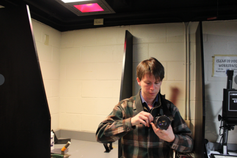 """Joshua Hunt poses in Homestead's darkroom. """"If I could only choose one class to teach it would probably be photography,"""" Hunt said """"I designed the class from the ground floor up, so  it more than any of the other classes that I teach is kind of my baby."""""""